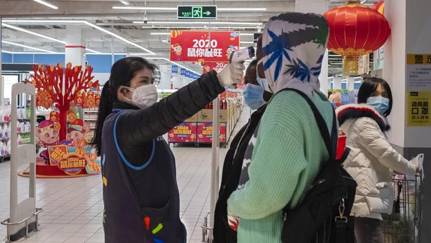 A worker takes the temperature of a customer at the entrance of a Walmart store in Wuhan in central China's Hubei Province (Arek Rataj/AP)
