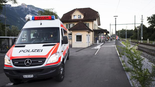 A police car is parked at a station following an attack on a train in Salez, Switzerland (Gian Ehrenzeller/Keystone via AP)