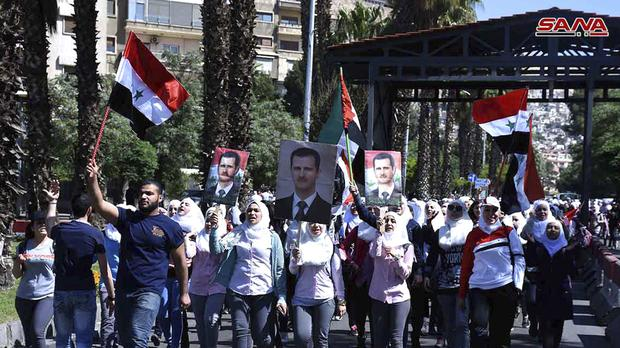 Pro-Assad demonstrators rally in Damascus (SANA/AP)