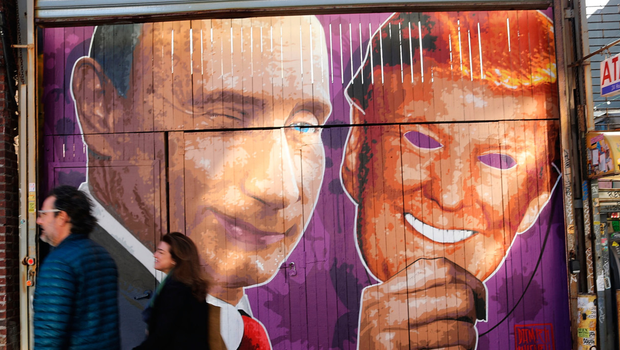 A mural depicting Vladimir Putin taking off a Donald Trump mask on a storefront in Brooklyn, New York Photo: Spencer Platt/Getty Images