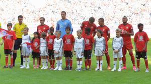 Bayern Munich players stand with refugee children on the pitch before the German Bundesliga match in the Allianz Arena in Munich (AP)
