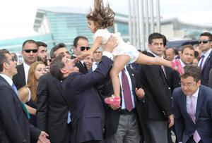 Turkish Prime Minister Ahmet Davutoglu (C) celebrates with the daughter of Turkey's Mosul Consul General Ozturk Yilmaz (not seen) during a welcoming ceremony at Esenboga airport in Ankara
