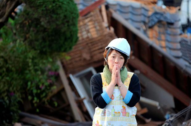 A resident stands in front of a damaged house in Mashiki, Kumamoto prefecture, southern Japan yesterday. Photo: Naoya Osato/Kyodo News