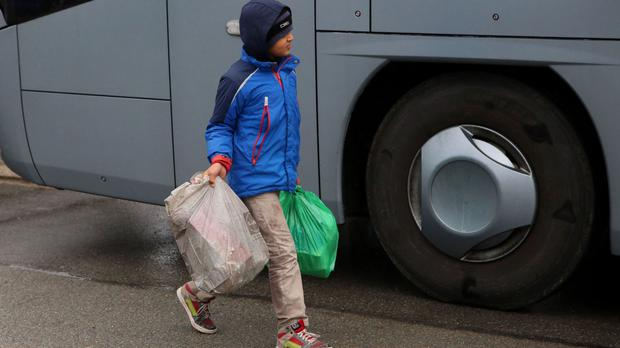 A young boy carries his belongings as families prepare to board a coach at the Jungle migrant camp in Calais, France