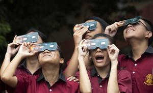 Students hold special filters to view the eclipse at the Santiratwitthayalai School in Bangkok, Thailand (Sakchai Lalit/AP)