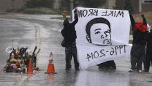 Protesters hold up a banner at a memorial in the middle of a street more than three months after a black 18-year-old was shot and killed there by a white policeman in Ferguson, Missouri (AP)