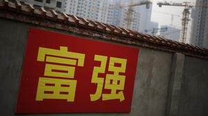 """Chinese government propaganda words which read """"Prosperity and Powerful"""" are displayed on a wall in Beijing (AP)"""