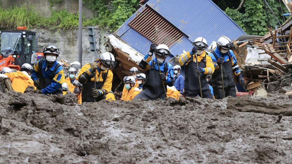 Police officers conduct a rescue and search operation at the site of a mudslide caused by heavy rain at Izusan district in Atami, Japan. Photo: Kyodo/via Reuters.