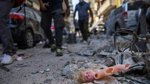 Failed state: People walk past a child's doll that was blown out of a nearby building