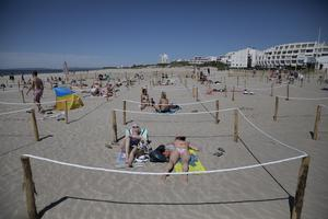 Sunbathers lay in areas marked out with ropes to enforce social-distancing measures in La Grande Motte in southern France (Daniel Cole/AP)