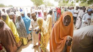 Voters queue in the harsh midday sun at a polling station in Daura, the home town of opposition candidate Muhammadu Buhari (AP)