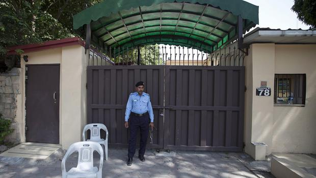 A police officer stands guard outside a sealed Save the Children office in Islamabad, Pakistan (AP)