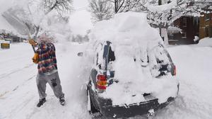 Kevin Deiner, of Erie, Pennsylvania, digs out his car buried on West Sixth Street (Jack Hanrahan/Erie Times-News via AP)