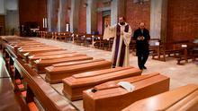 MASS BURIAL: A priest blesses the coffins of deceased people in the church of San Giuseppe in Seriate, Lombardy, yesterday. Photo: Piero Cruciatti/AFP