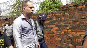 Philip Blackwood, manager of V Gastro bar, is escorted by police to his trial in Yangon, Burma (AP)