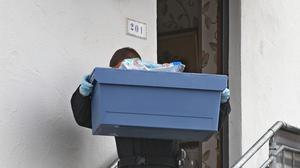 A policeman carries evidence from a house in Augsburg, southern Germany (AP)