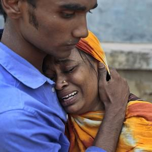 Relatives mourn a victim at the site after an eight-storey building housing several garment factories collapsed in Savar, near Dhaka, Bangladesh (AP)