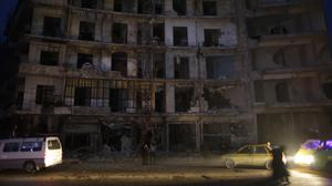 People walk next to a destroyed building in the once rebel-held Shaar neighbourhood in Aleppo, Syria (AP/Hassan Ammar)