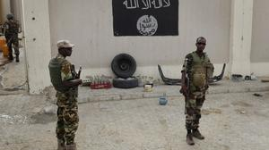 Chadian soldiers stand at a checkpoint in front of a Boko Haram flag in the Nigerian city of Damasak. (AP)