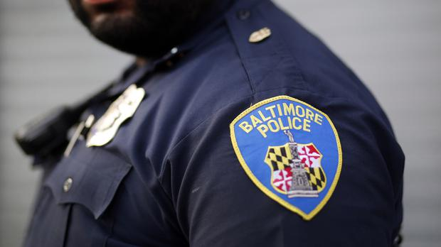 A Baltimore Police Department Officer stands on a street corner (AP)