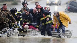 Emergency officials transport James Simmons by boat because water over Byler Road prevented them from reaching him in Moulton, Alabama (The Decatur Daily/AP)