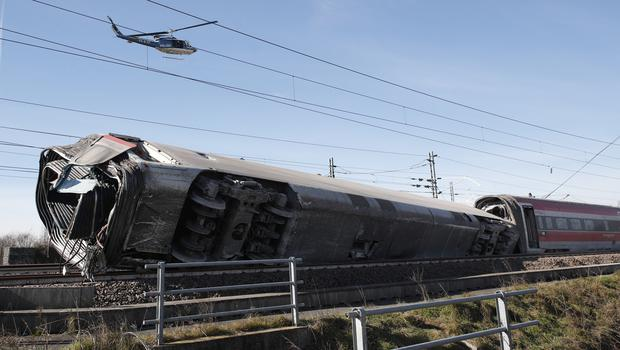 A police helicopter flies over an overturned carriage of a high-speed train which derailed in the countryside near the town of Lodi, northern Italy (Antonio Calanni/AP)