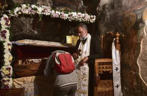 A believer kisses the remains of St Basil in the Christian Orthodox monastery of Ostrog (Risto Bozovic/AP)