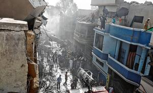 Crash scene: Search teams begin to carry out their task in the Model Colony area of Karachi