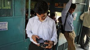 An Indian man surfs the internet on his smartphone as he travels in a local train in Mumbai. (AP)