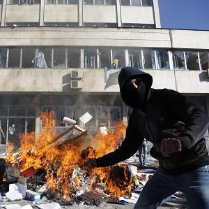 A Bosnian protester sets a local government building on fire during protests in the town of Tuzla (AP)