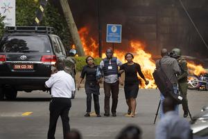 Security forces help civilians flee the scene at the hotel complex in Nairobi (Ben Curtis/AP)