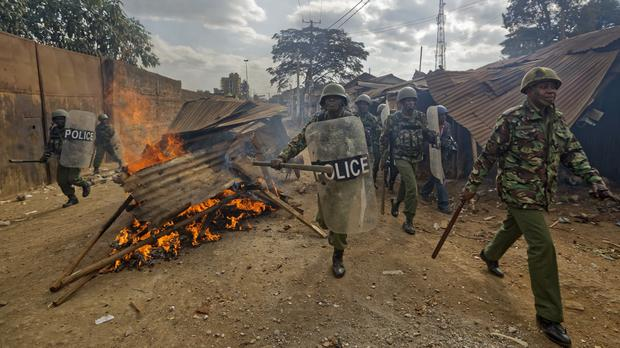 Riot police walk past burning barricades erected by protesters throwing rocks during clashes in the Kawangware slum of Nairobi (Ben Curtis/AP)