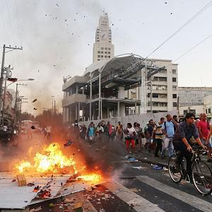 Commuters walk past a burning barricade set by demonstrators protesting against a hike in bus fares, outside a train station in Rio de Janeiro (AP)