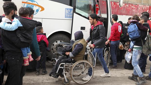 Members of the Syrian Red Crescent help opposition fighters and their families leave the al-Waer area of Homs (AP)