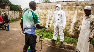 A health worker sprays disinfectant on a colleague after handling a suspected Ebola sufferer in Freetown. (AP)