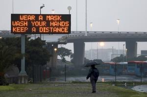 A man walks beneath a sign advising precautions people should take to prevent the spread of coronavirus in Cape Town (Nardus Engelbrecht/AP)