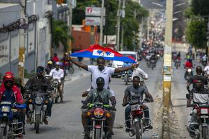 A protester holds up a Haitian national flag (Dieu Nallo Chery/AP)