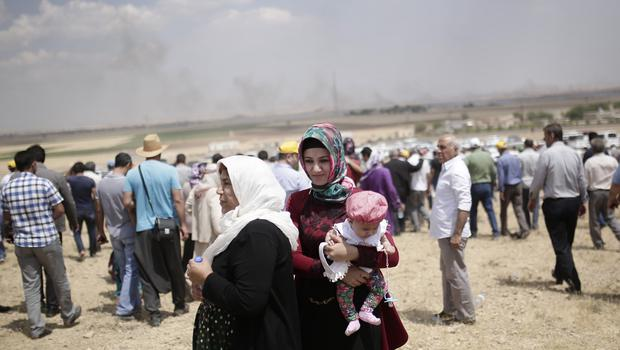 People standing on the Turkish side of the border watch as smoke rises over Kobani, in Syria (AP)