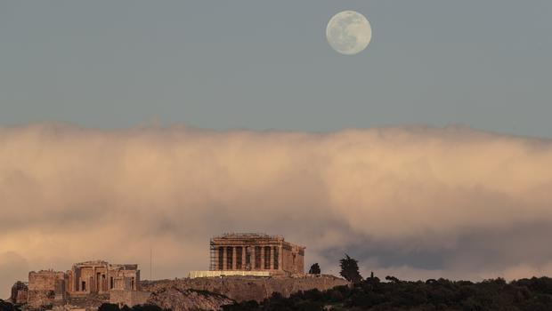 The moon rises behind the ancient Acropolis hill with the 500 BC Parthenon temple in Athens (Petros Giannakouris/AP)