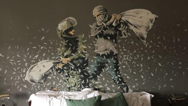 A bedroom in a new guesthouse shows artwork by Banksy in the West Bank (AP)