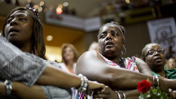 Barbara Lloyd, of Charleston, joins hands with mourners at a memorial service for the victims of the shooting (AP)
