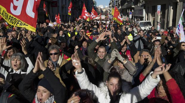 CGT Union protesters march at a demonstration during a mass strike in Marseille, southern France, Tuesday, Dec. 10, 2019. French airport employees, teachers and other workers joined nationwide strikes Tuesday as unions cranked up pressure on the government to scrap upcoming changes to the country's national retirement system. (AP Photo/Daniel Cole)