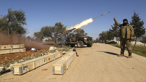 Rebel fighters fire a missile towards Syrian government positions in the province of Idlib (Ghaith Alsayed/AP)