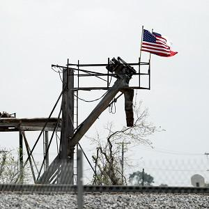 Flags fly over the West Fertiliser Co. explosion site in West, Texas. Law enforcement officials have launched a criminal investigation into the massive fertiliser plant explosion that killed 14 people last month (AP)