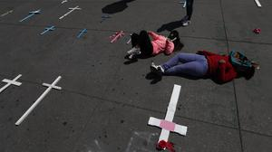 """Women lie next to a crosses set in remembrance of murdered women in Mexico City's main square the Zocalo, during the International Women's Day strike """"A day without women,"""" Monday, March 9, 2020. Thousands of women across Mexico went on strike after an unprecedented number of girls and women took to the streets to protest against unbridled gender violence on International Women's Day. (AP Photo/Marco Ugarte)"""