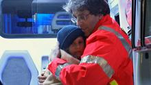 A child rescued from the Hotel Rigopiano is hugged by a rescue worker. Photo: Reuters