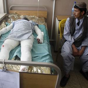 An Afghan man visits a wounded relative in hospital in Kandahar, after the deadly bus crash (AP)