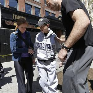 Aaron Herns takes a few steps with the help of his mother and father as they visit the area of the second bombings where Aaron was injured (AP Photo)