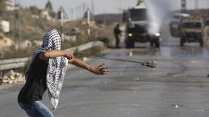 A Palestinian uses a slingshot to throw stones towards Israeli troops. (AP)