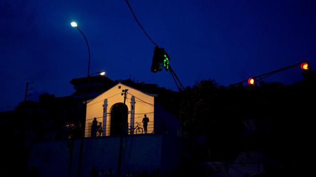 People are silhouetted against the facade of a church, the only building illuminated after a 24-hour blackout, just outside of Caracas, Venezuela (AP)